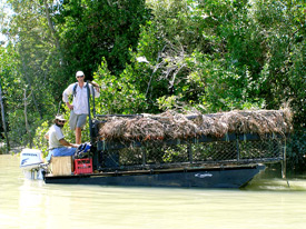 Briano and Trevor heading up river to set a floating trap